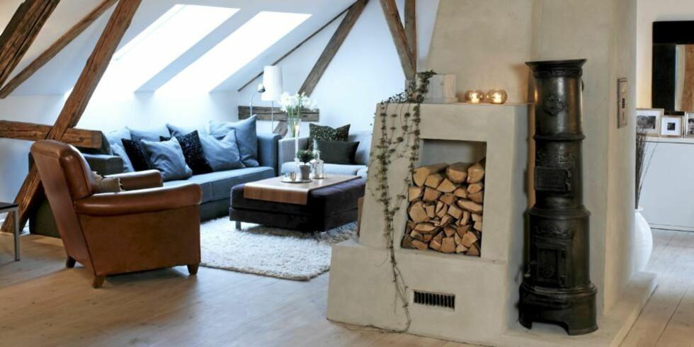 LOFTSSTUE: Vedkubbene har egen oppbevaringsplass på siden av peisen. I stedet for salongbord er det valgt en puff med flyttbar plate over.  FOTO: Espen Grønli