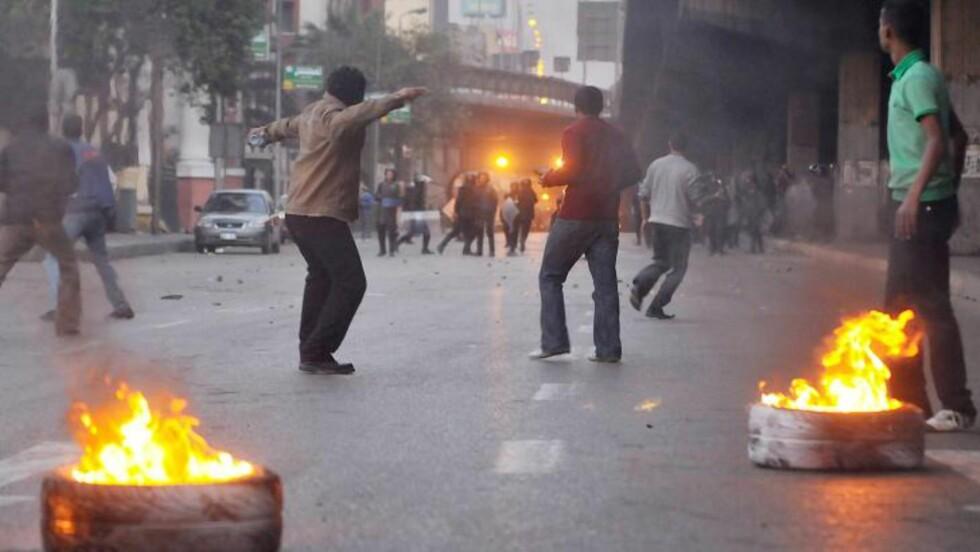 I BRANN:  Demonstranter har satt fyr på bildekk i sentrum av Kairo i kveld. FOTO: EPA/SCANPIX.