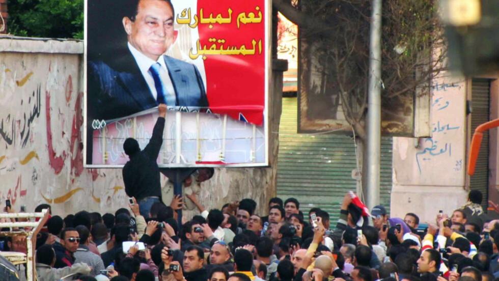 PRESIDENT UNDER PRESS:  Demonstranter i millionbyen Alexandria river ned en plakat av Hosni Mubarak. Selv har ikke den 82 år gamle presidenten gitt livstegn siden uroen startet for alvor. FOTO: AFP/SCANPIX.