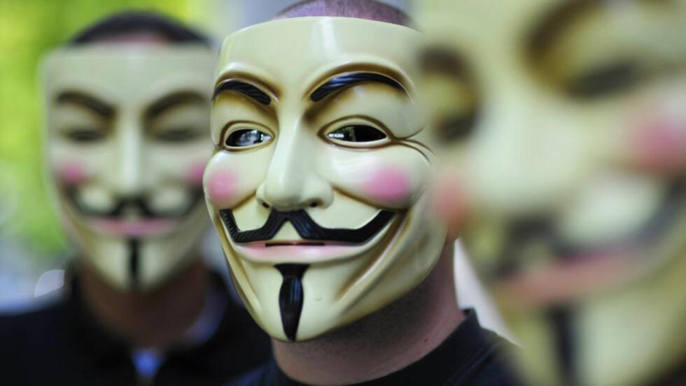 HACKERANGREP:  Aktivister fra organisasjonen Anonymous går til angrep mot egyptiske myndigheters nettsider. Her er aktivister avbildet med den typiske Anonymous-masken, som har blitt deres varemerke. Foto: AFP PHOTO