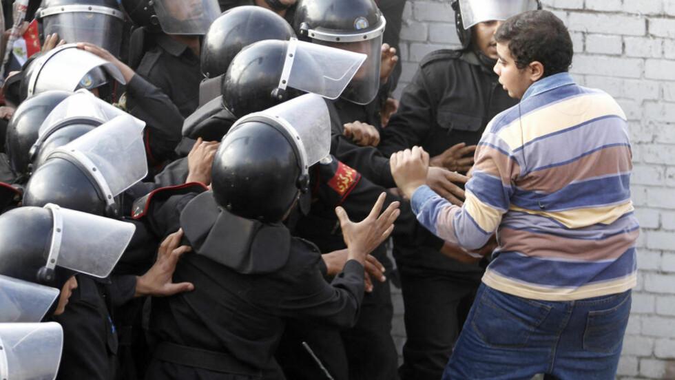 GJØR MOTSTAND: En demonstrant forsøker å gjøre motstand mot politistyrker i Kairos gater. I dag er det varslet nye demonstrasjoner. Foto: REUTERS  / Mohamed Abd El-Ghany