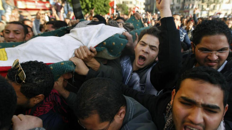 DREPT:  Demonstrantene bærer vekk en mann som døde i forsøkene på å storme innenriksdepartementet i går. Hvor mange som mistet livet i kampene ved departementsbygningen er uvisst. Foto: REUTERS/Yannis Behrakis