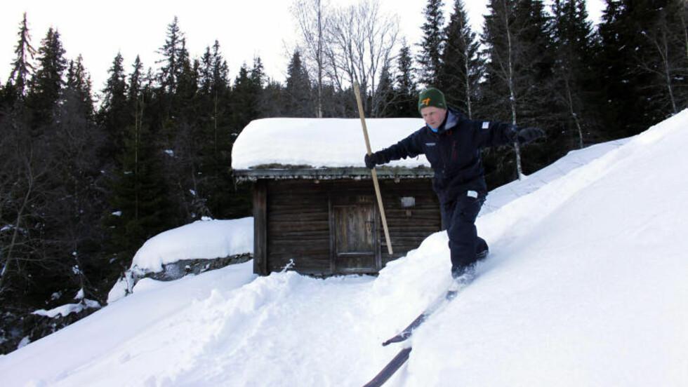 ØVERBØ: Tarjei Gjelstad demonstrerer skikjøring à la Sondre foran den lille stua på husmannsplassen Øverbø. Foto: OLE C. H. THOMASSEN