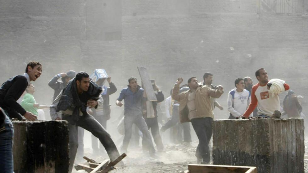 Regimet vakler: Opprøret mot Mubaraks regime fortsetter. Demonstranter i Kairo kaster stein mot Mubarak-tilhengere. Foto: AFP/SCANPIX