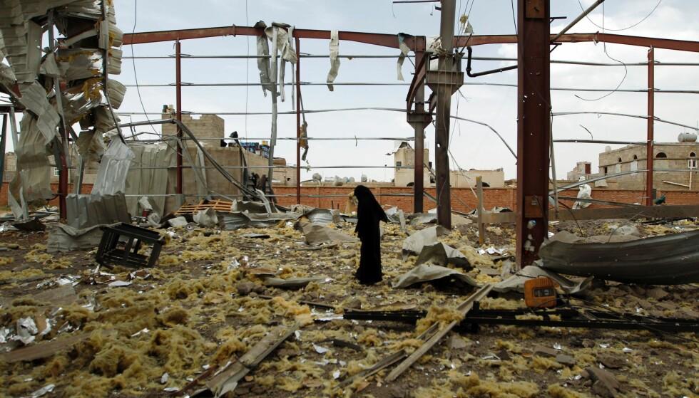VOLDSOM KRIG: En kvinne går rundt i ruinene av det som en gang var en fabrikk i Jemens hovedstad Sanaa. Den saudi-ledede koalisjonen har nå vært i krig i Jemen i halvannet år. Fremdeles selger Norge våpenmateriell til partene. Foto: Mohammed Huwais / Afp / Scanpix