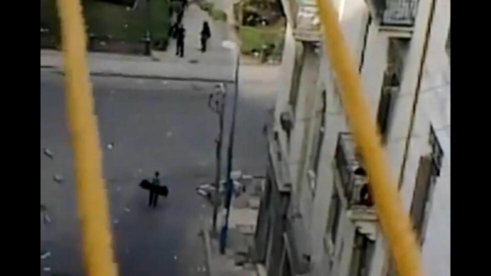 TAR AV SEG JAKKA: Mannen tar av seg jakka, som for å vise at han er ubevæpnet, og gestikulerer for politiet. Deretter høres skudd, og mannen faller i bakken. Episoden skal ha skjedd i Alexandria fredag 28. januar. Foto: Youtube