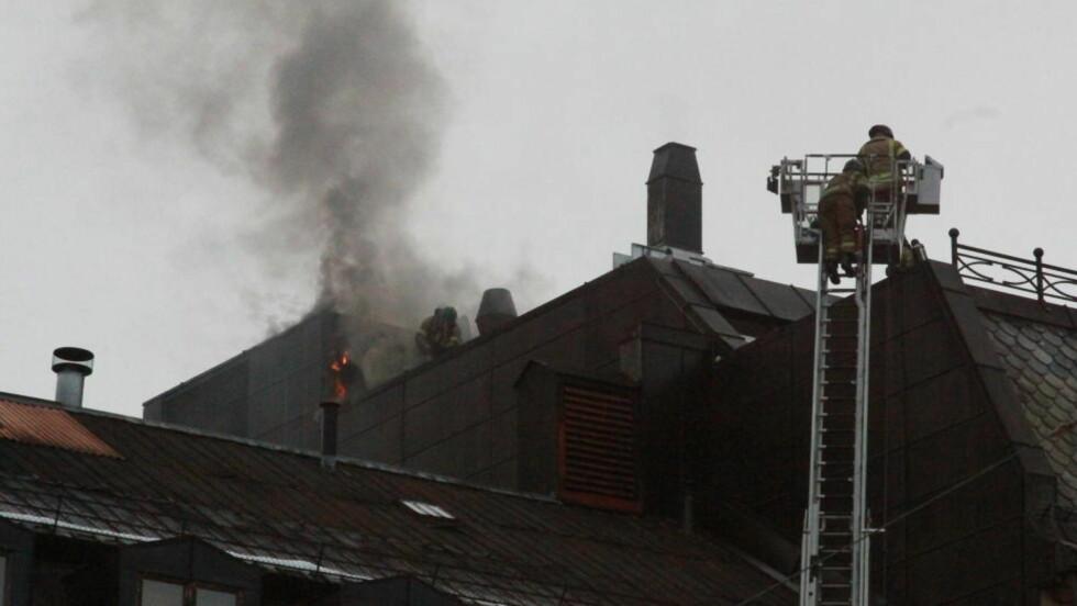 BRENNER:  Brannvesenet jobber med å slokke brannen i taket av Hard Rock Café. Foto: Odd Grytebust