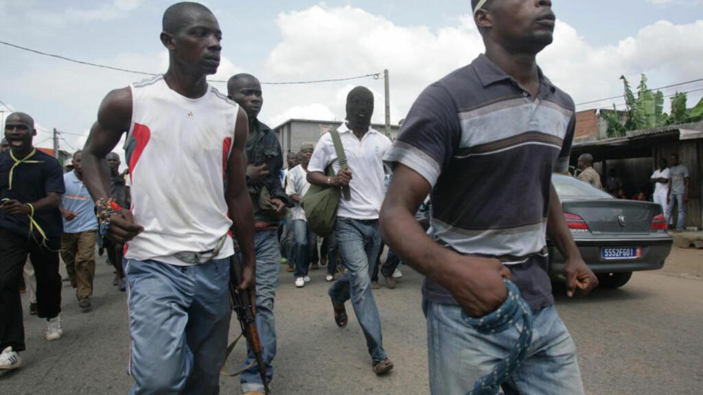 MED VÅPEN: Tilhengere av president Laurent Gbagbo har bevæpnet seg med hjemmelagde våpen og gevær for å gå til angrep mot opprørerene. Foto: SCANPIX/AP/EMANUEL EKRA