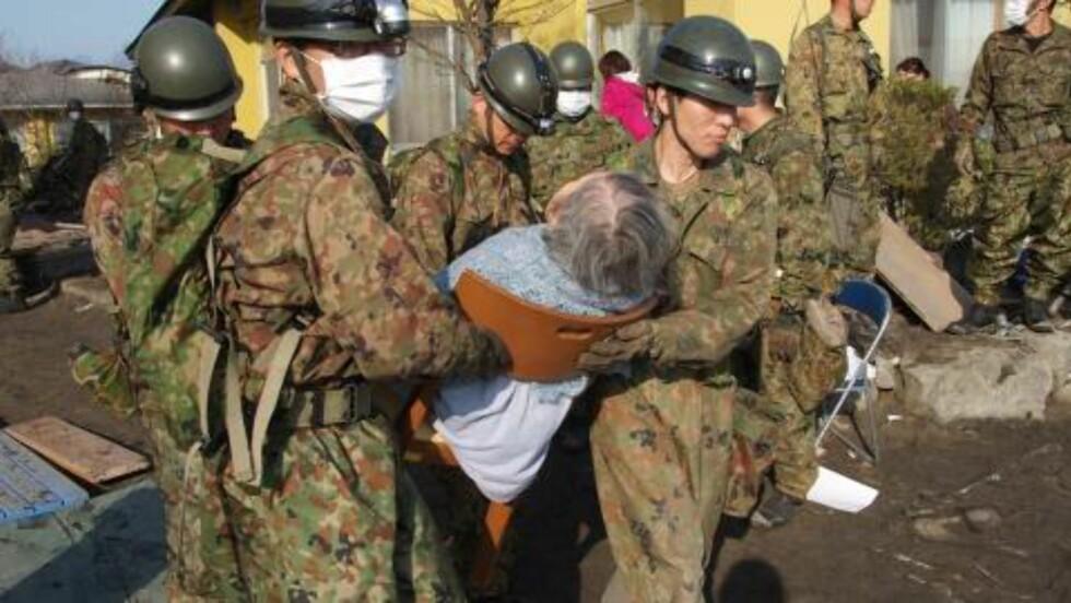 DØDSTALLLENE STIGER:  En eldre kvinne får hjelp av japanske hjelpemannskaper i Miyagi-distriktet i går. I dag meldes det om funn av så mange omkomne, at antallet som er bekreftet døde dobles. EPA/JAPAN SELF DEFENSE FORCES