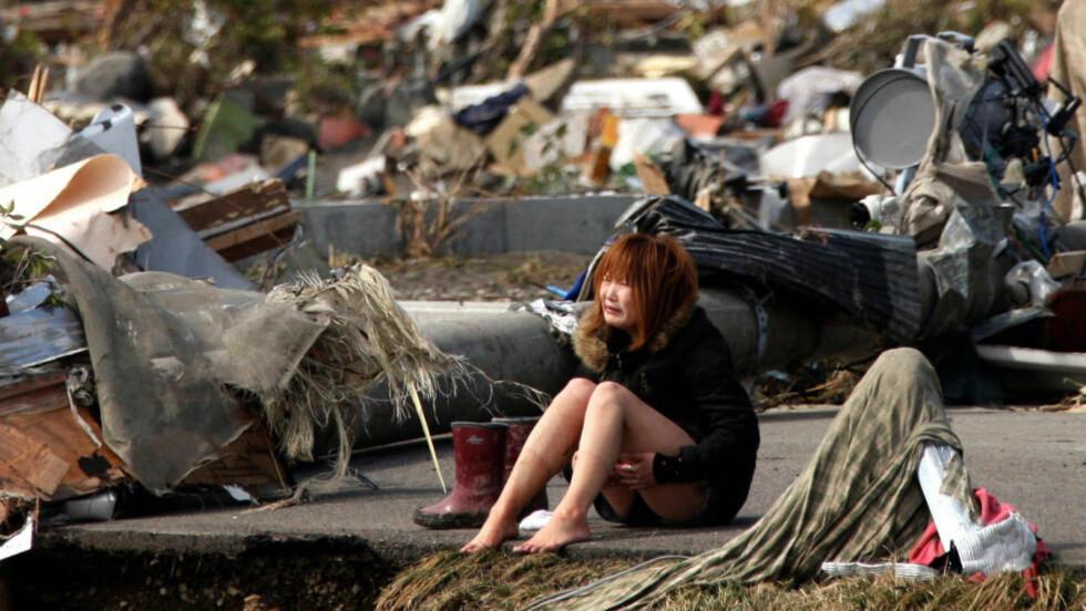 JAPAN I SORG:  En kvinne gråter blant restene av byen Natori, som er ødelagt av jordskjelv og tsunami. REUTERS/Asahi Shimbun