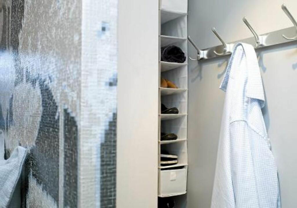 OPPBEVARING: Bak veggen har interiørarkitekten plassert et høyskap og en stoffhylle, begge fra Ikea. Løsningen er identisk på hver side, slik at paret får hvert sitt personlige skap. Foto: Espen Grønli
