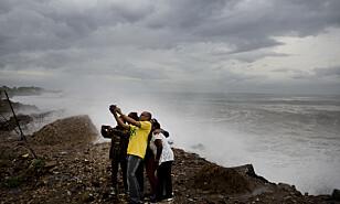 STORM-SELFIE: På en strand i utkanten av Kingston, Jamaica, står en liten gruppe og tar selfie foran orkanen Matthew. Både Jamaica, Haiti og Cuba vil merke orkanens herjinger. Foto: Eduardo Verdugo / Ap / Scanpix