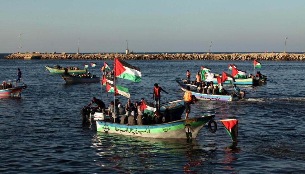 - ARRESTERT: Totalt 13 personer skal være arrestert, blant dem en norsk kvinne, etter at et israelsk marinefartøy bordet aktivistbåten «Zaytouna-Oliva». Bildet viser palestinere som var på vei ut for å ønske båten velkommen onsdag. Foto: Ashram Amra / Zuma Press / NTB Scanpix