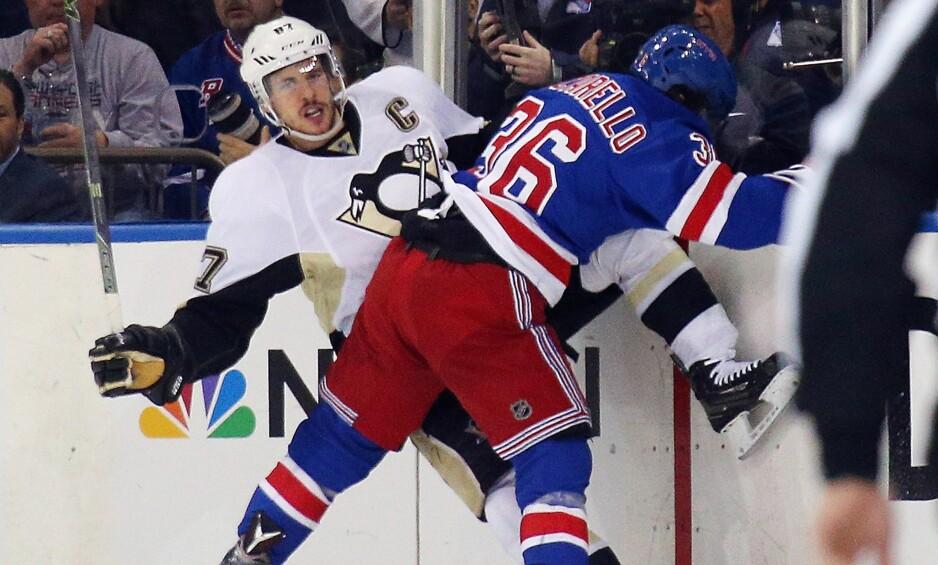 SKADET: Sidney Crosby har pådratt seg en hjernerystelse, og blir ikke å se i NHL-starten. Her blir han taklet av Mats Zuccarello Aasen i Stanley Cup-playoff tidligere i år. Foto: Bruce Bennett/Getty Images/AFP