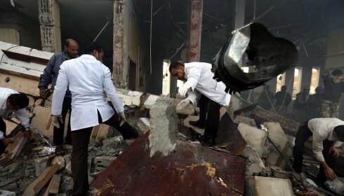 LETER ETTER OMKOMNE: Hjelpearbeidere leter etter mennesker i ruinene av samfunnshuset i Sanaa. Foto: Osamah Abdulrhman / Ap / Scanpix