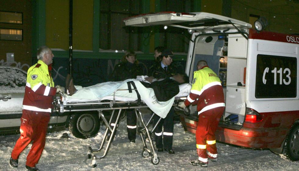 BRUTALT: En av de tre personene som ble skadet i knivstikkingen på moskeen, blir her fraktet til en ambulanse. Foto: Morten Holm / SCANPIX .