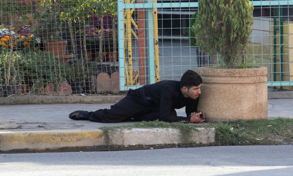 GJEMMER SEG: En kurdisk sikkerhetsvakt ligger i skjul og følger med på at IS-folk angrep offisielle kontor i Kirkuk i morges. Foto: Ako Rasheed / Reuters / Scanpix