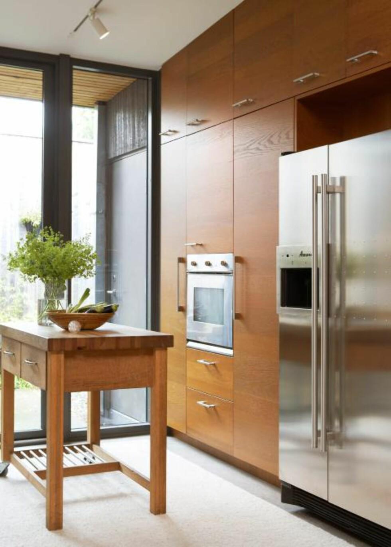 SKREDDERSØM: Kjøkkeninnredningen i tre og stål er fra Ikea. Treskapene er tilpasset i høyden slik at de går helt opp til taket, som er svakt hellende. FOTO: Margaret M. de Lange