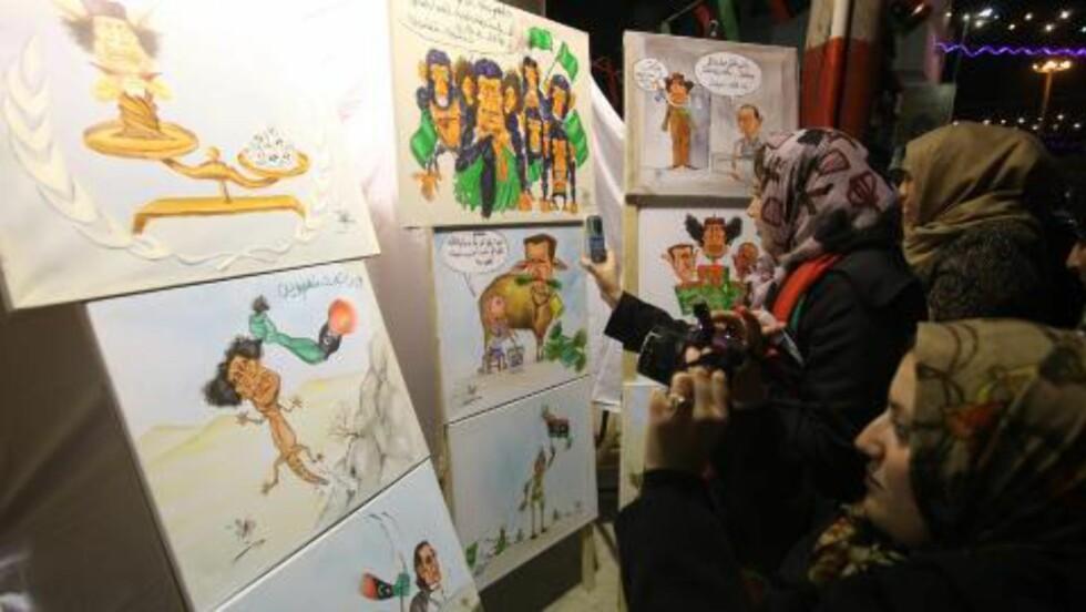 GLEMMER IKKE:  En rekke libyere ønsker ikke lenger fokus på Muammar Kadhafi, og vil se framover. Men samtidig er det tusenvis av fantastiske tegninger, malerier og veggmalerier over diktatoren, som styrte Libya med jernhånd i hele 42 år. Her er bilder plassert ut i hovedstaden Tripoli i går. Foto: Sabri Elhedwi / EPA / Scanpix
