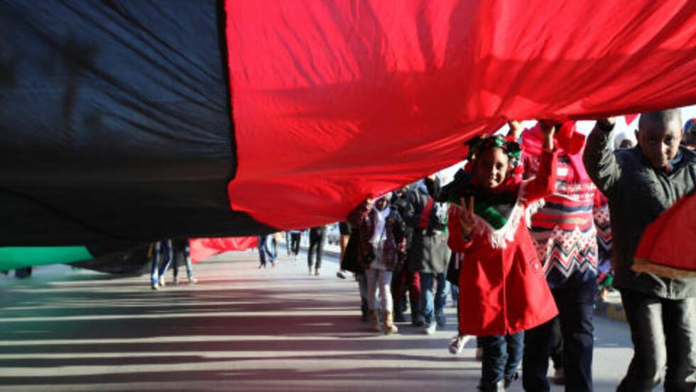 KREATIVE:  Under tredagers-feiringen er barn, unge og voksne dekorert med det libyske flagget, som var forbudt under Muammar Kadhafi. Kjempeflagg, luer, lommebøker, sokker og skjerf ... Alt i de karakteristiske røde, svarte, grønne og hvite libyske flaggfargene. Foto: Mohammad Hannon / Ap / Scanpix