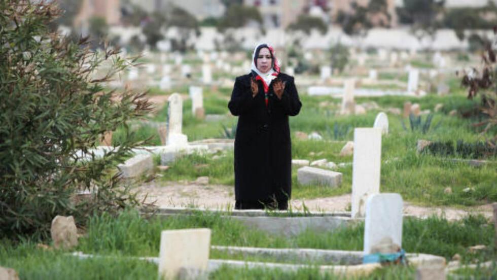 HEDRER DE DØDE:  En kvinne leser et vers fra Koranen ved sønnens grav i Benghazi i går. Et fremdeles ukjent antall tusen libyere mistet livet under kampen for å bli kvitt Muammar Kadhafi. - Nå gjelder det å hedre de døde. Vi må skape et nytt Libya vi alle kan være stolte over, sier veldig mange libyere. Foto: Reuters / Scanpix