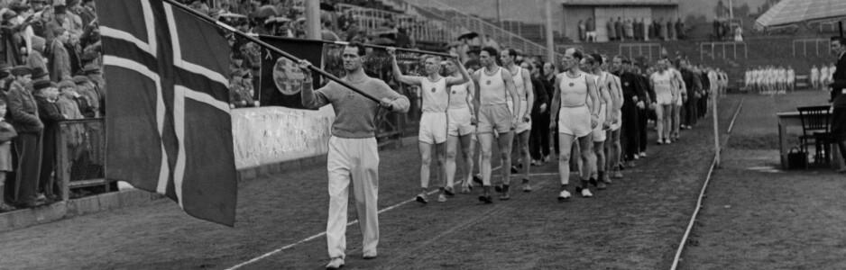Oslo 1944. Defilering på Bislett Stadion etter den vellykkede hirdstafetten. De omkring 1000 deltakerne med Charles Hoff som flaggbærer, passerer ærestribunen. Foto: Aftenposten