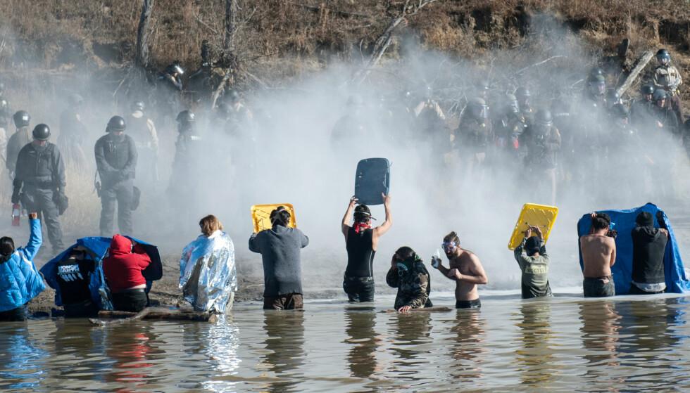 HEFTIGE PROTESTER: Politiet har blitt satt inn mot demonstranter mot en oljerørledning i indianerreservatet Standing Rock i delstaten North Dakota, og hundrevis har blitt arrestert og skadet. På dette bildet fra 2. november bruker politiet tåregass mot demonstrantene Foto: REUTERS/Stephanie Keith