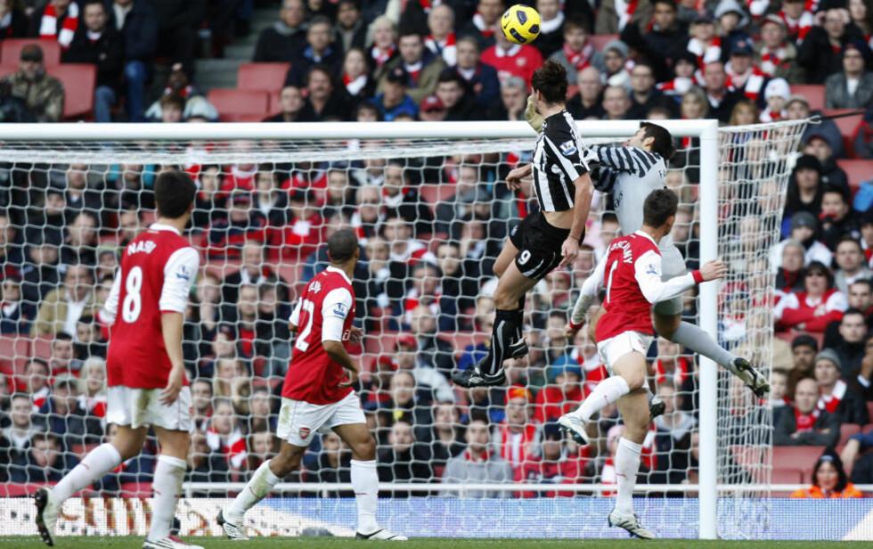 RAGET HØYT OVER FABIANSKI: Andy Carroll viste fryktinngytende spenst da han knuste Arsenal-keeperen i lufta, og scoret på Newcastles første avslutning i kampen. Foto: AP Photo/Kirsty Wigglesworth