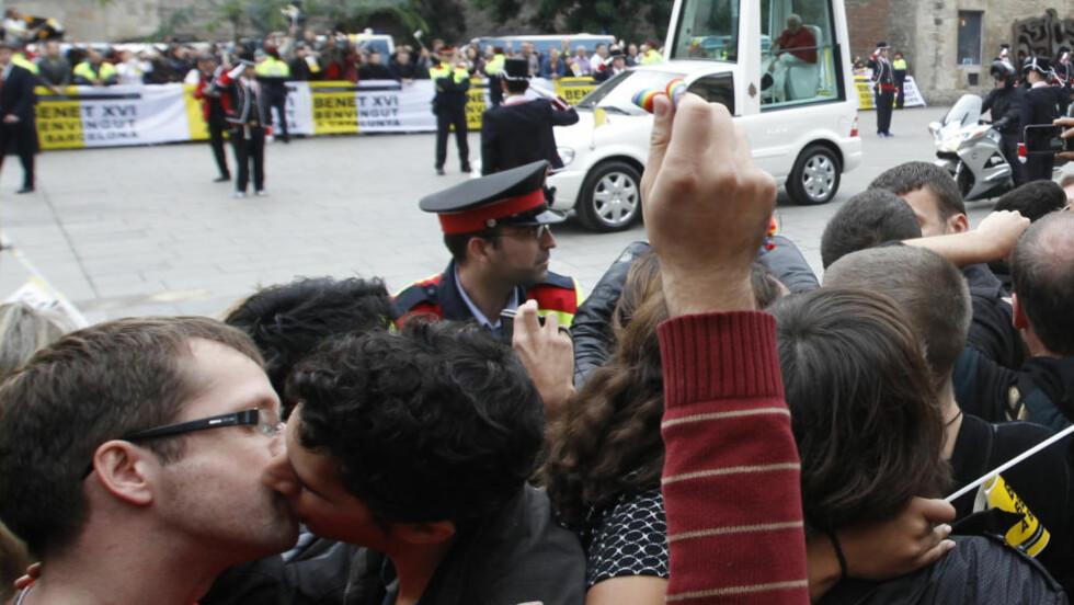 PAVEPROTEST:På vei til kirken Sagrada Familia i Barcelona søndag ble pave Benedikt XVI møtt av blant andre kyssende homofile som protesterte mot den katolske kirkens holdninger til homofili. Foto: REUTERS / Gustau Nacarino / SCANPIX