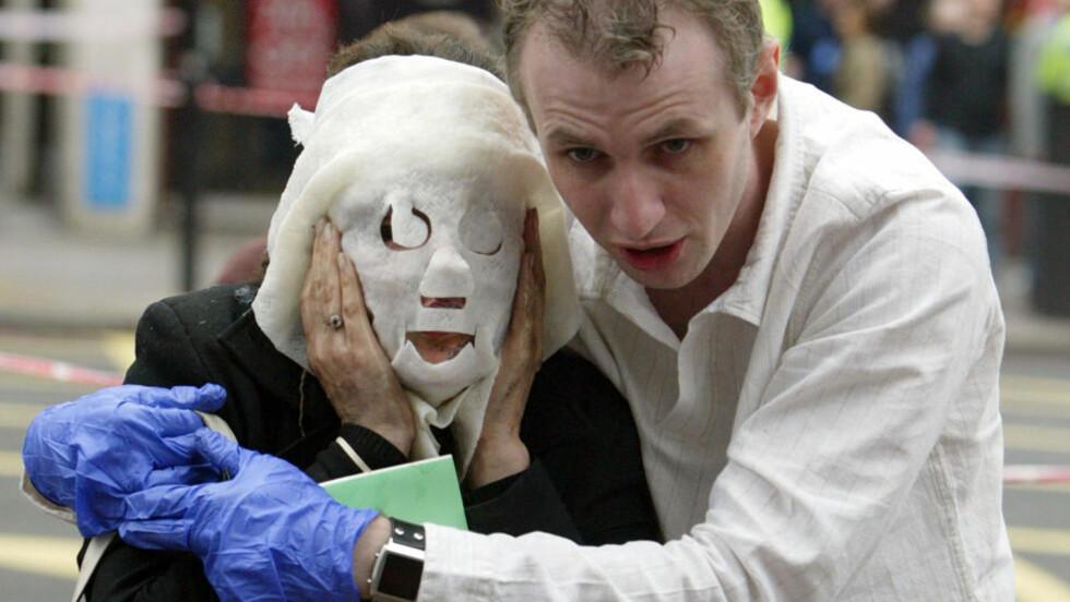 LONDONBOMBINGEN: Paul Dedge hjelper passasjeren Davinia Turrell vekk fra t-banestasjonen Edgware Road etter terrorangrepet i London. Totalt 52 mennesker mistet livet i 7. juli-angrepet. Foto: AP Photo/Jane Mingay