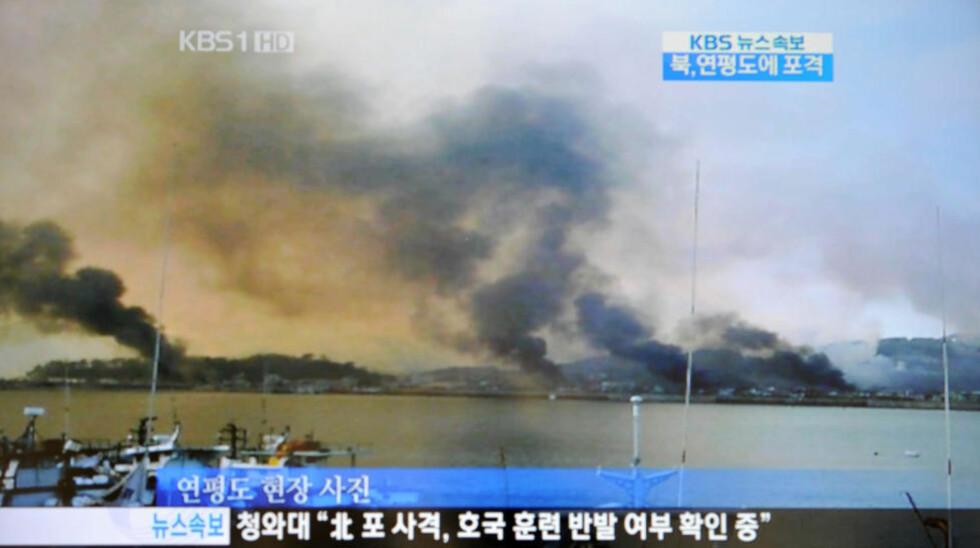 I BRANN: Bildet er fra den sørkoreanske TV-kanalen KBS, og viser røyken som stiger fra øya Yeonpyeong etter det nordkoreanske granatangrepet. Foto: AFP PHOTO/KBS OFF TV