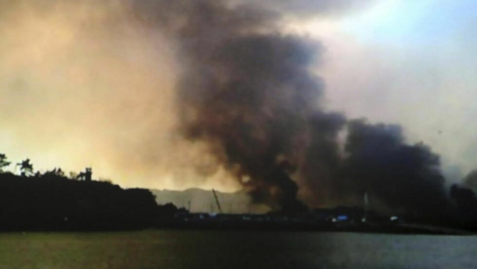 ÉN DREPT: Røyken stiger fra Yeonpyeong etter en rekke granatangrep fra Nord-Korea. Så langt er det meldt at én sørkoreansk marinesoldat er drept i angrepene. Foto: AP
