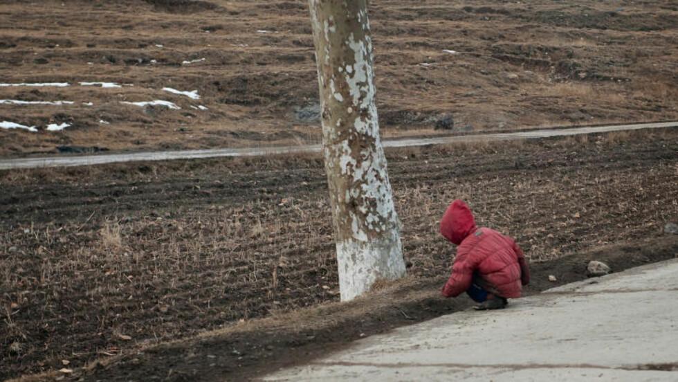 FATTIG: En liten gutt sitter i veikanten. Det finnes knapt trær i Nord-Korea på grunn av mangel på brennstoff. Dette fører igjen til en rekke oversvømmelser og flommer, som ødelegger veier, bruer og matjord. Foto: Røde Kors
