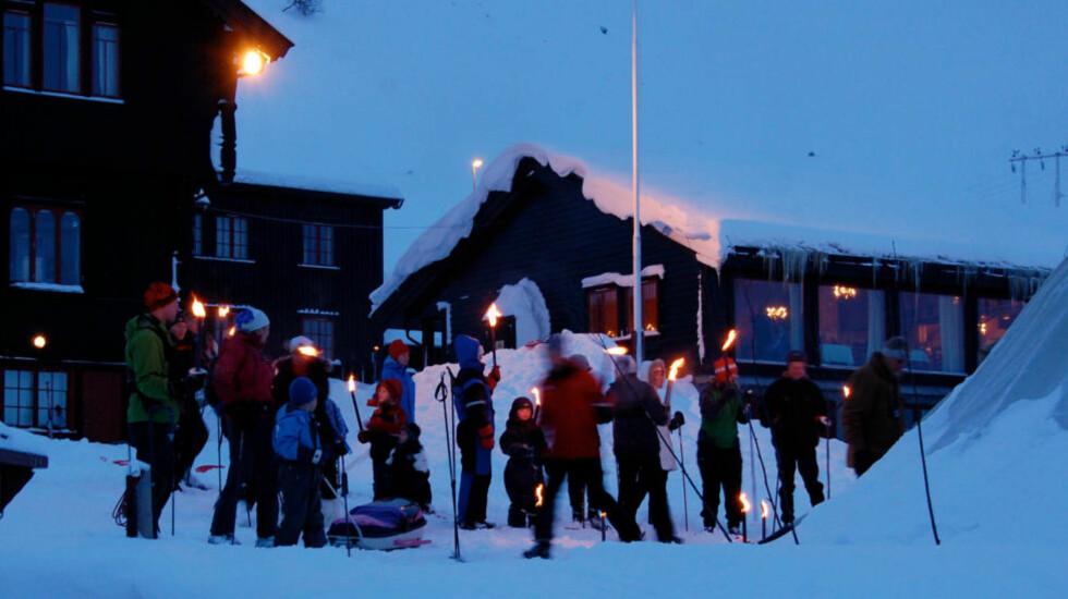 SKUMRINGSTUR: Med fakler i den blå timen til fjells på Turistforeningens helårsåpne Haukeliseter. Foto: Haukeliseter fjellstue