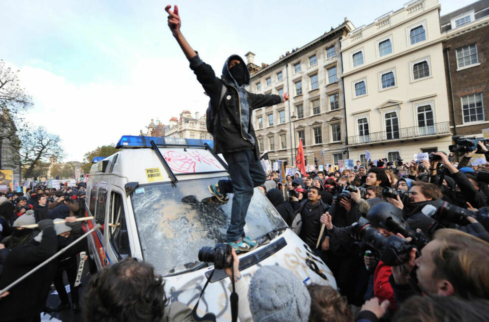 VRAK: En politibil ble stående midt i folkemengden på Whitehall - og ble dermed et lett bytte for de mest aggressive av studentdemonstrantene. Foto: Anthony Devlin/PA/AP/Scanpix