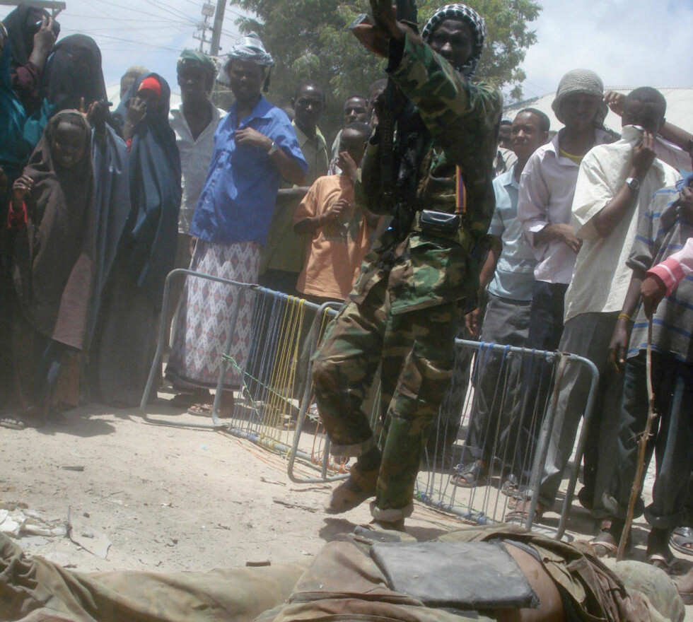 HVERDAGEN: En al-shabaab-kriger står over liket av en AU-fredssoldat drept i sammenstøt mellom partene i Mogadishu, mens sivile flokker seg rundt. Foto:  AFP Photo/Abdurashid Abikar/Scanpix