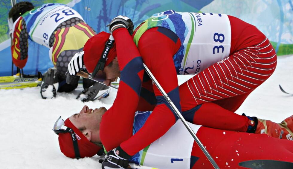 UTSLITT OG GLAD: Petter Northug har stupt i bakken som OL-mester på femmila. Lagkompis Odd-Bjørn Hjelmeseth er raskt framme og gratulerer lagkameraten. Foto:  Arnt E. Folvik, Dagbladet