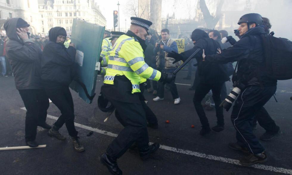 VOLDSOMT: Rasende studenter markerer klart hva de synes om regjeringens planer. Én politimann skal være hardt skadd i opptøyene i London sentrum. Foto: Stefan Wermuth/Reuters/Scanpix