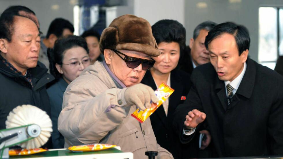 ATOMKRIG OG SJOKOLADE : Dette bildet av Nord-Koreas leder Kim Jong-Il ble offentliggjort av Nord-Koreas sentraliserte nyhetsbyrå KCNA i dag - samme dag som den avbildedes ledelse advarer mot atomkrig i regionen. Om det er i dag Jong-Il skal ha undersøkt matpakkene på Sonhung Foodstuff Factory i Pyongyang, er uvisst. Foto: KCNA/AFP.
