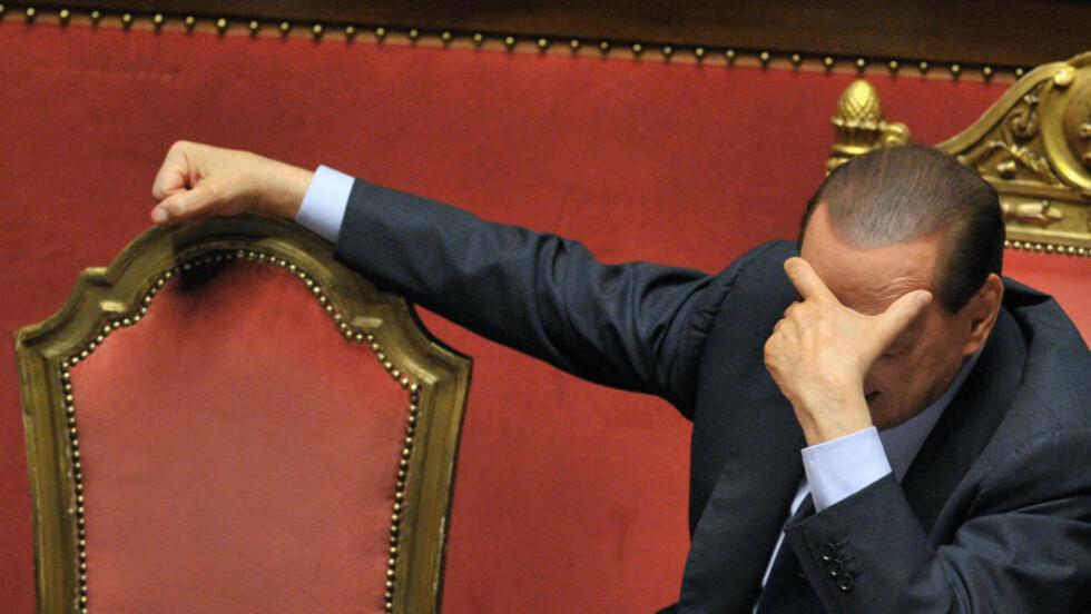 SKANDALEOMBRUST: Italias statsminister Silvio Berlusconi kjemper for sitt politiske liv. Her fortviler han under en debatt i det italienske overhuset i dag. Foto: Scanpix