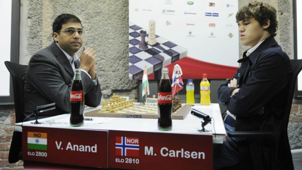 TOK TILBAKE POSISJONEN SOM VERDENSENER: Magnus Carlsen vil igjen være nummer én når det internasjonale sjakkforbundet, FIDE, presenterer den offisielle verdensrankingen ved nyttår. Dermed ble det et kort opphold på toppen for indiske Viswanathan Anand (t.v.). Foto: SCANPIX/AFP PHOTO/ RAFA RIVAS