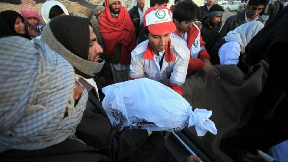 MINST SYV DØDE:  Innbyggere og redningsmannskap frakter bort døde personer etter at et jordskjelv som målte 6,5 på Richters skala rammet Kerman-provinsen i Iran. Foto: EPA/HAMID SADEQI