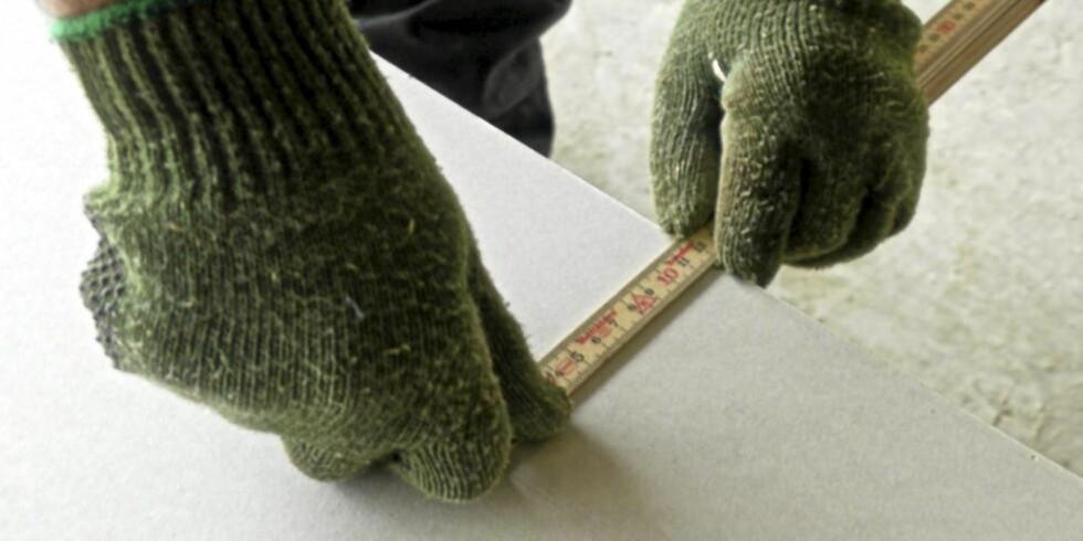SLIK GJØR DU DET: Med den ene tommelen som anlegg for å styre tommestokken og med tapetkniven (skjult i den venstre hånden) mot enden av tommestokken, er det bare å dra kniven bortover gipsplaten. Foto: Øivind Lie