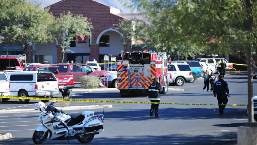 Åstedet:Politiet og redningsmanskaper på åstedet utenfor supermarkedet der kongressmedlem Gabrielle Giffords, og flere andre ble skutt i dag i Tucson, Arizona. Foto: AP/Chris Morrison)