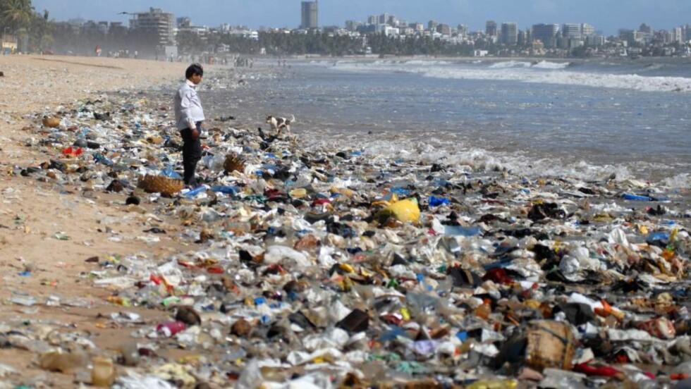 FULLT AV PLAST: En man ser på Juhu Beach i Mumbai, India. Bildet er fra i dag. Foto: EPA/DIVYAKANT SOLANKI