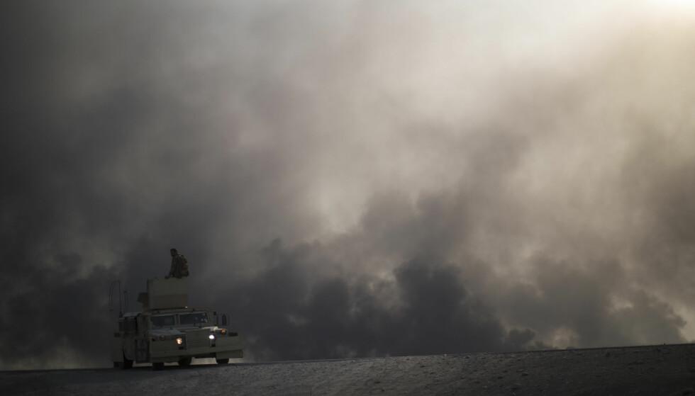 KAMPEN OM MOSUL: En pansret bil og irakiske soldater er på vei mot byen Hamam al-Alil, sør fra Mosul. Hele 1500 familier skal ha blitt tvunget ut av hjemmene sine og mot flyplassen, ifølge FN. Foto: Felipe Dana / Ap / Scanpix