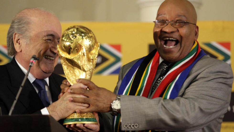 TO GLADE GUTTER: Jacob Zuma og Sepp Blatter med VM-trofeet på en pressekonferanse i Pretoria. Begge to har økonomiske svin på skogen. Foto: AP/Themba Hadebe/Scanpix
