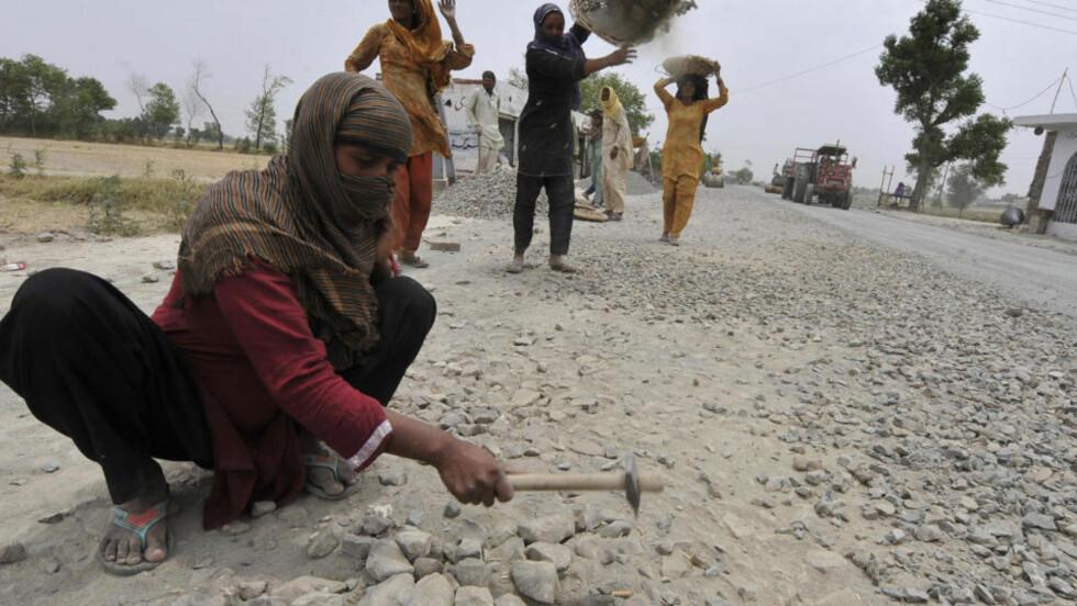 FATTIGDOM: Pakistanske Ayesha Bibi (t.v) jobber her med å lage en vei fra Wazirabad til Daska (193 km) sørøst forIslamabad 18. mai 2010. 29-åringen er enke og firebarnsmor og gravid med sitt femte barn. Å jobbe er den eneste måten hun kan forsørge barna. Pakistan er trolig et av de verste landene for kvinners helse. Over 115 millioner enker over hele verden lever i fattigdom, ifølge en ny studie. Foto: AFP Photo/Aamir Qureshi/Scanpix