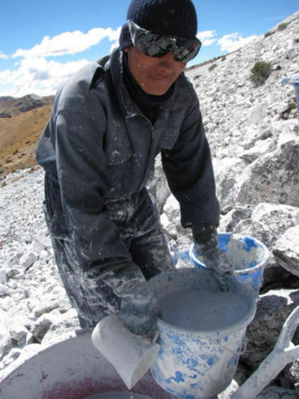 <strong>TAR TID:</strong> Arbeiderne bruker bøtter - ikke pensler - for å dekke steinene i hvitfarge. Foto: AFP PHOTO/DAN COLLYNS/SCANPIX