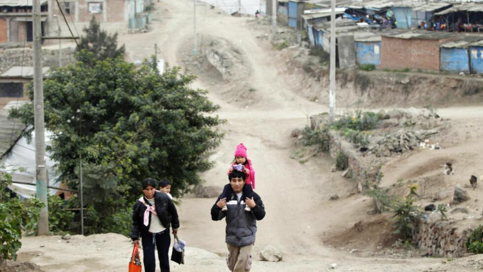 <strong> KALDT:</strong> Tykke klær og topplue er påkrevd for denne jenta på farens skuldre i et fattig område i Perus hovedstad Lima. Myndighetene har iverksatt en helsekampanje, særlig innrettet mot barna, og erklært unntakstilstand i 16 provinser på grunn av kulden. FOTO:ENRIQUE CASTRO-MENDIVIL /REUTERS/SCANPIX